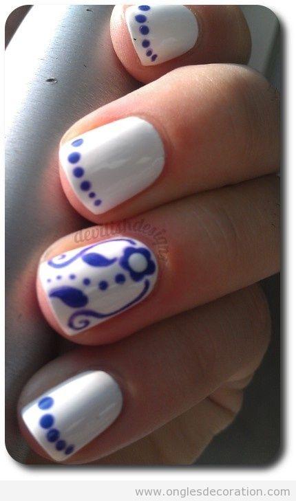 Dessin sur ongles, fleurs et poids bleu sur blanc